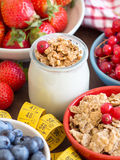 Jar of fresh yogurt, berries, muesli and measuring tape Stock Photo