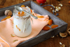 Jar of fresh yogurt with nuts and apricots on an old tray Stock Images