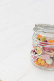 Jar full of candies. Open glass jar full of different colourful jelly candies on white wooden background Stock Images