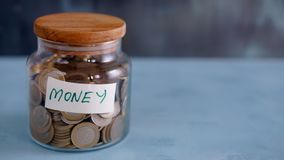 Jar full of coins on a black background - saving money royalty free stock photo