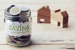 Jar with full of coins inside with wooden house model background. Home finance concept. Jar with full of coins inside with wooden house model background. Saving royalty free stock images