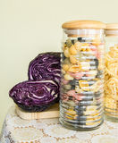 Jar full of colorful pasta and red cabbage on the side on a decorated table cover Stock Images