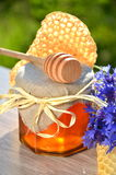 Jar full of delicious fresh honey piece of honeycomb honey dipper and wild flowers Royalty Free Stock Photography