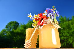 Jar full of delicious fresh honey, piece of honeycomb honey dipper and wild flowers in apiary Stock Photo