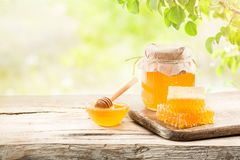 Jar full of fresh honey and honeycombs. On a wooden background Stock Image