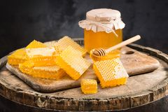 Jar full of fresh honey and honeycombs. On a wooden background Stock Images