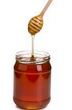 Jar full of honey and stick Stock Photography