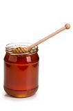 Jar full of honey and stick Stock Photos