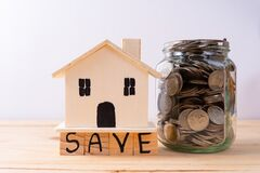 Free Jar Full Of Coins With Save Word Paper And Wooden House On Wooden Table Isolated Grey Background. Saving Money And Investment Stock Image - 216658411