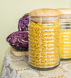 Jar full of pasta and red cabbage on the side on a decorated table cover Royalty Free Stock Photos