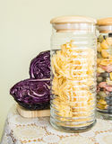 Jar full of pasta and red cabbage on the side on a decorated table cover Royalty Free Stock Images