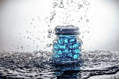A jar of gel beads with water splashes Stock Images