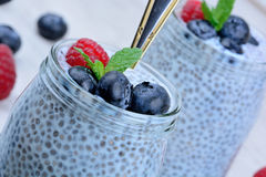 Jar glass with chia seeds pudding with berries on table Stock Photos