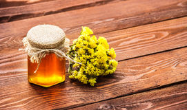 A jar of golden honey on an old table. Homemade sweets and desserts. Royalty Free Stock Photo