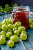 Jar of gooseberry jam on a wooden table. Royalty Free Stock Photos