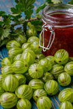 Jar of gooseberry jam on a wooden table. Stock Image