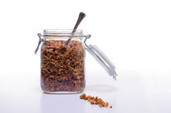 Glass Jar of Granola. Glass jar containing healthy home made granola. Photographed against a white background Stock Photo