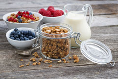 Jar with granola, milk, and fresh berries on the wooden table. Horizontal Royalty Free Stock Image