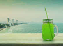 Jar with green ice drink and straw on wooden table over sea, Vin Stock Images