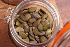 Jar of green pumpkin seeds. Overhead view on glass canning jar with green roasted pumpkin seeds Stock Image