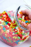 Jar and handful of jelly beans. Vertical crop of clear open jar and handful of colorful jelly beans Royalty Free Stock Images