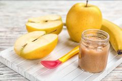 Jar with healthy baby food and apple. On wooden board stock images
