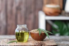 Jar with hemp oil and bowl of seeds stock image