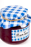 Jar of home-made plum jam. Home made plum jam  in glass jar with checked blue paper cover and hand written labels. On white Royalty Free Stock Photos
