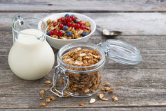 Jar with homemade granola, milk and fresh berries. On wooden table, horizontal Royalty Free Stock Image