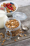 Jar with homemade granola, milk and fresh berries. On wooden table, top view, vertical Royalty Free Stock Images