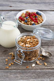 Jar with homemade granola, milk and fresh berries. On wooden table, vertical, top view Royalty Free Stock Photography