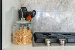 Jar of granola next to modern gas stovetop with kitchen utensils and marble tile backsplace in the backgroud. Bright, royalty free stock images