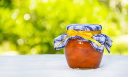 A jar of homemade jam on a white table. Sweet gift from my grandmother. Summer desserts. Copy space royalty free stock photo