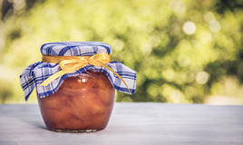 A jar of homemade jam on a white table. Sweet gift. Summer desserts. Copy space royalty free stock photography