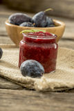 Jar of homemade plum jam with wooden bowl of juicy ripe fresh pl Royalty Free Stock Photo