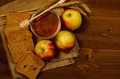 Jar of honey, apples, rye bread, ears on sacking, wooden table Royalty Free Stock Images