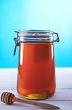 Jar of honey on a blue background Royalty Free Stock Images