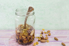 Jar of honey with choped nuts, almond and hazelnuts. Healthy dessert in a jar Stock Photo