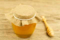 Jar of honey closed jute cloth drizzler on wooden background Stock Images