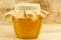 Jar of honey closed jute cloth on wooden background Royalty Free Stock Photos