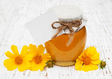 Jar of honey with cosmos flowers Royalty Free Stock Photography