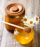 Jar of honey with daisy flowers Stock Photos