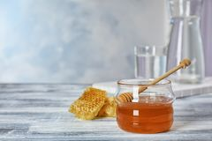 Jar of honey and dipper. On table stock image