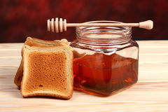 Jar of honey, dipper and toast Stock Photography