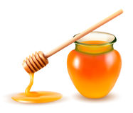 Jar of honey and a dipstick. Royalty Free Stock Photography