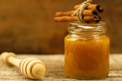 Jar of honey with drizzler and cinnamon on wooden background Stock Images