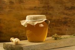 Jar of honey with drizzler, jute fabric, dried flowers on wooden background Royalty Free Stock Photography