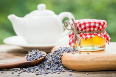 Jar of honey, dry healthy lavender tea and teapot on background. Royalty Free Stock Photos
