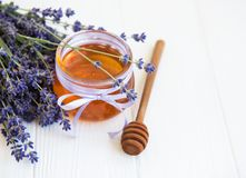 Jar with honey and fresh lavender flowers. On a white wooden table stock photo