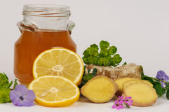 Jar of honey and ginger. Honeycomb, ginger, sliced lemons, herbs, flowers and a jar of honey stock photo